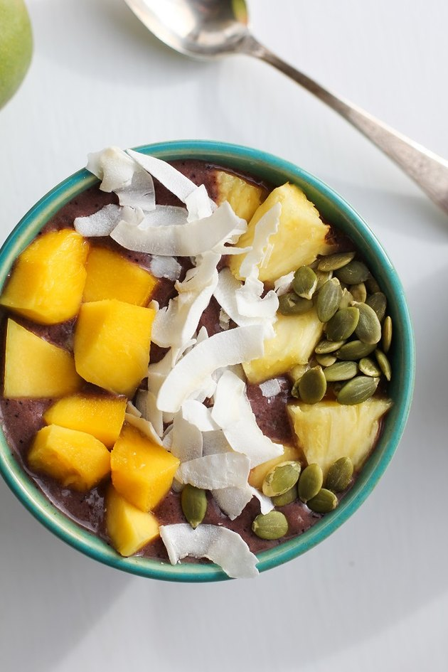 Acai bowl with mango, pineapple, coconut and pumpkin seeds