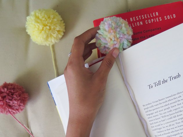 Place the yarn pompom at the top of the book page.