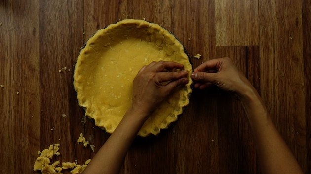Preparing gluten-free, low-carb coconut flour rolled pie crust for baking by fluting edges.