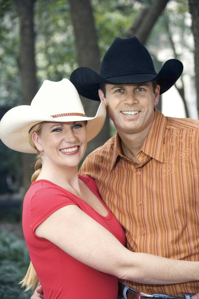 Couple wearing cowboy hats posing outdoors