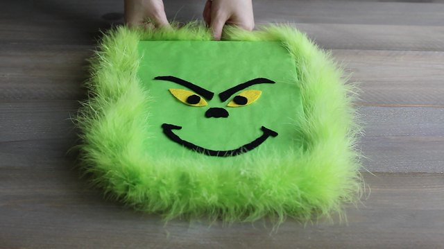 Wrapping green feather boa around perimeter of gift box