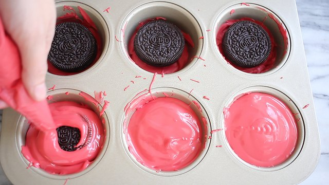 Piping melted red chocolate on top of Oreos