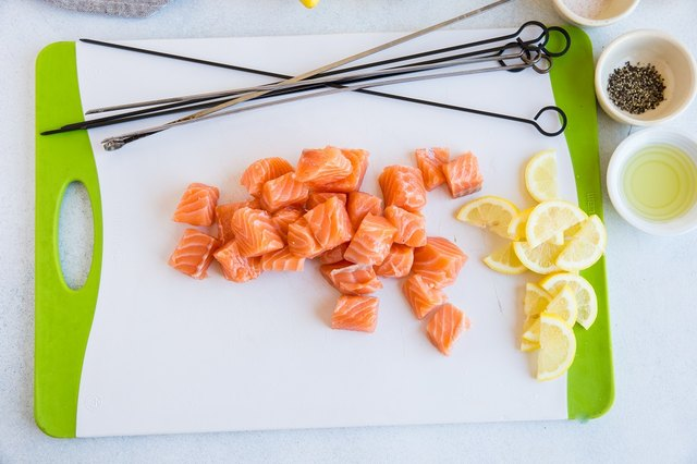 Chopped salmon and sliced lemon on a cutting board