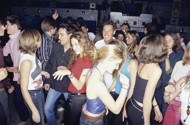 Large group of young adults dancing in club
