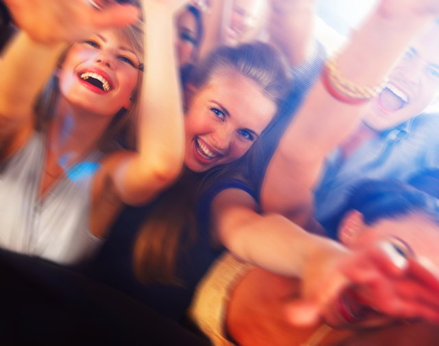Happy young boys and girls enjoying at disco