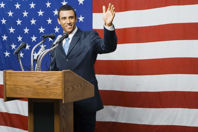 Political candidate at podium by American flag