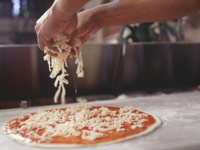 Man making pizza on table, close-up, surface view