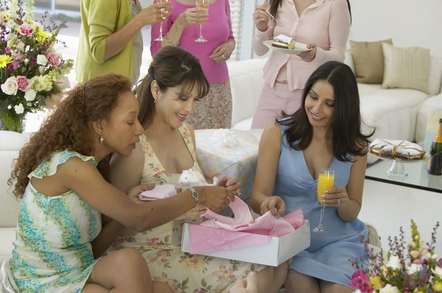Group of women at baby shower, three sitting on sofa opening gift