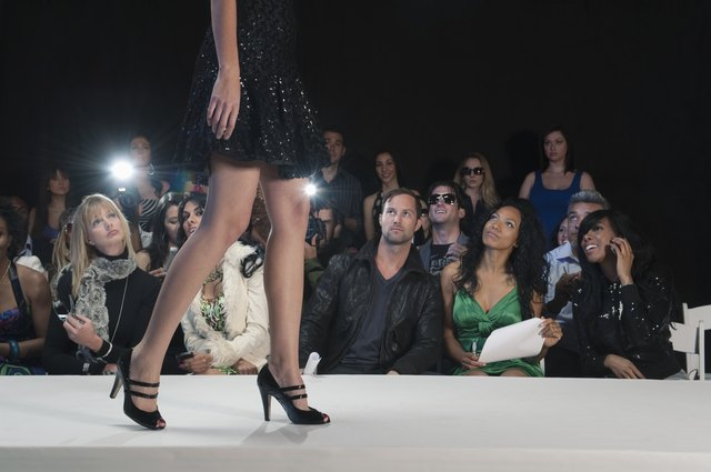 Low section of womans walking in black high heeled shoes on fashion catwalk