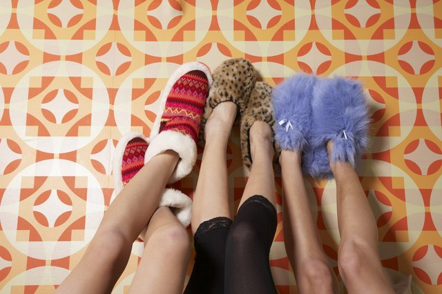 Two young women and teenage girl (16-17) wearing slippers, feet up against wall, low section