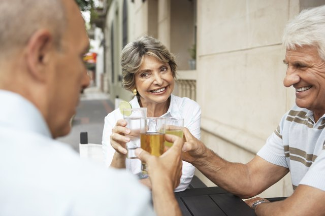 Senior woman and two senior men raising glasses, outdoors, close-up