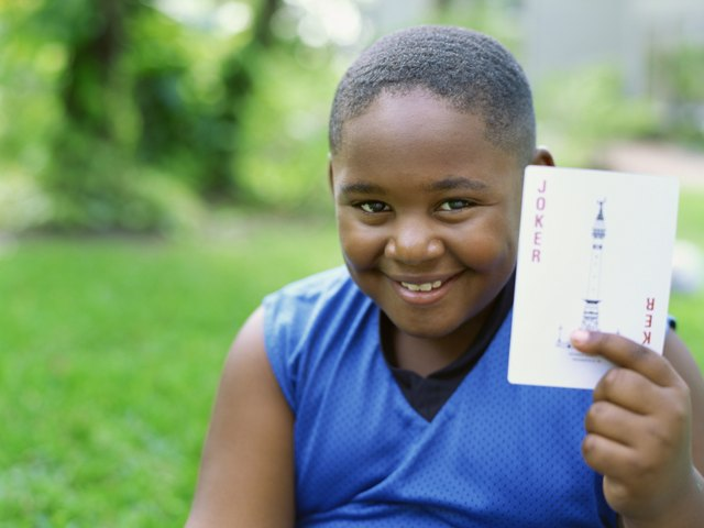 Portrait of a boy holding a joker card
