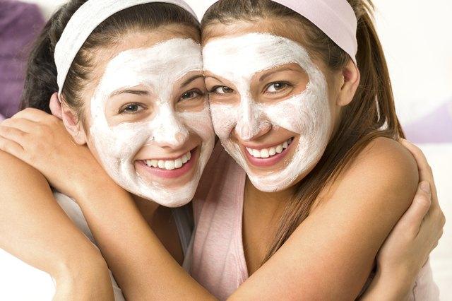 Blissful girls applying mask hugging each other