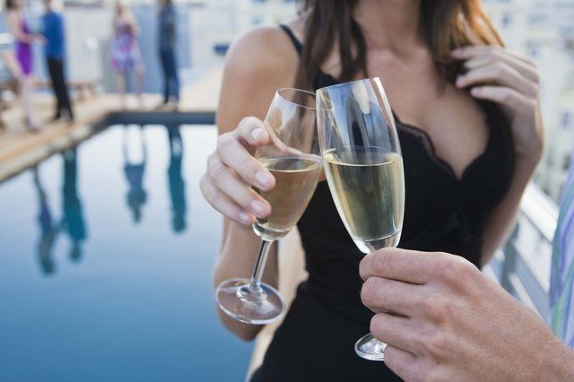 Couple toasting champagne poolside