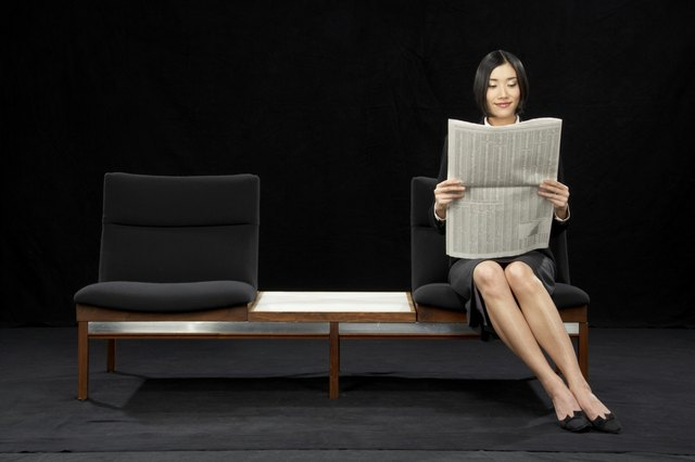Businesswoman sitting on bench reading newspaper, smiling