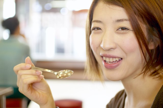 Woman holding spoon in restaurant
