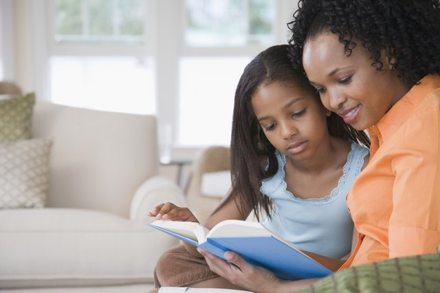 Side profile of a mid adult woman reading a book with her daughter and smiling