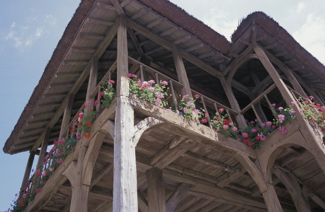 Low angle view of cottage with balcony and flowers