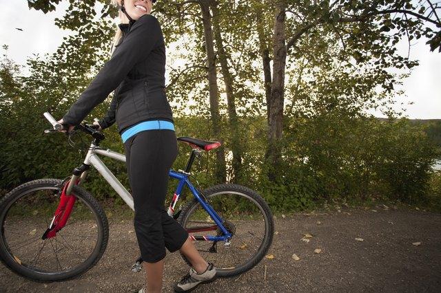 Smiling young woman mountain biking