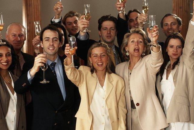 Business people raising glasses, smiling