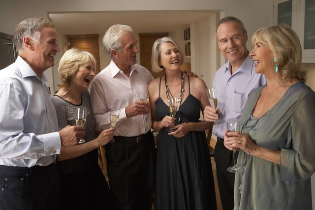 Friends Enjoying A Glass Of Champagne At Dinner Party