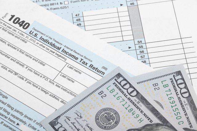 Tax Form 1040 with two 100 dollars banknotes