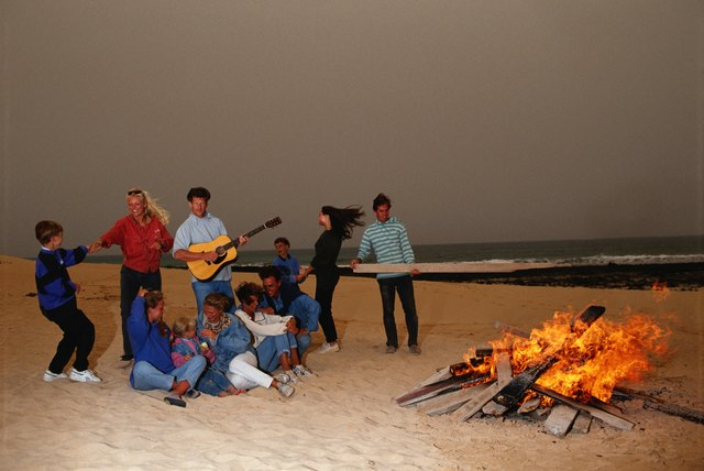 Group of people dancing around fire, man playing guitar