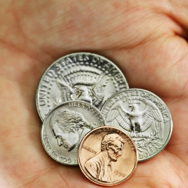 Close-up of a human hand holding various American denominations