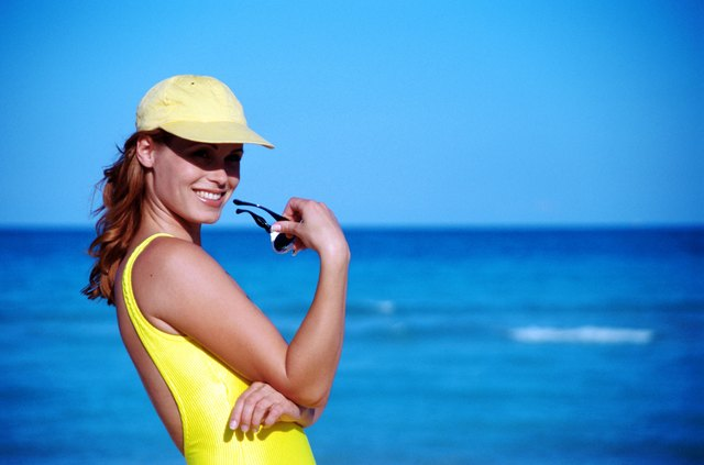 Young woman wearing cap and holding sunglasses on beach, smiling
