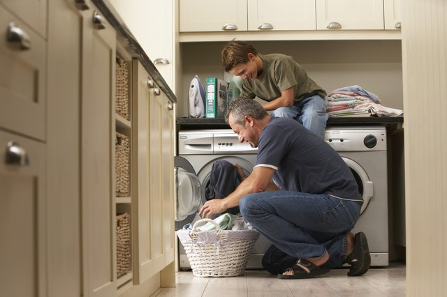 Father and son (9-11) loading washing machine, smiling