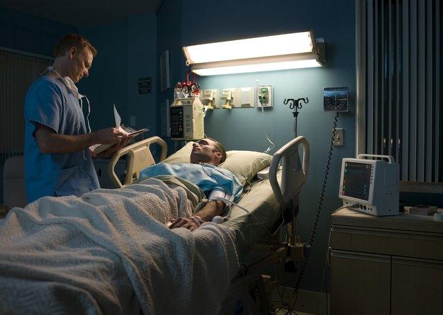 Doctor examining patient in hospital room