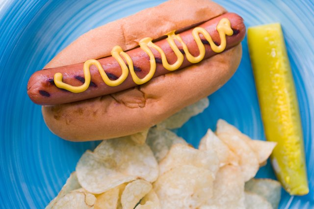 High angle view of hot dog with chips and pickle on plate
