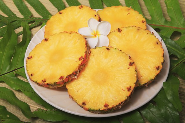 Ripe juicy Pineapple slices on platter with plumeria sitting on green leaves