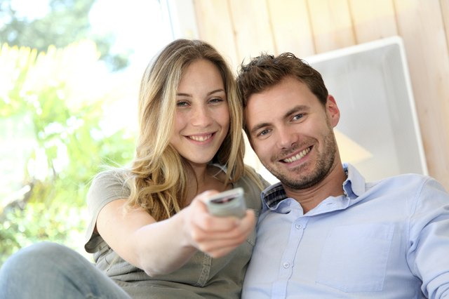 Smiling couple at home relaxing with tv film