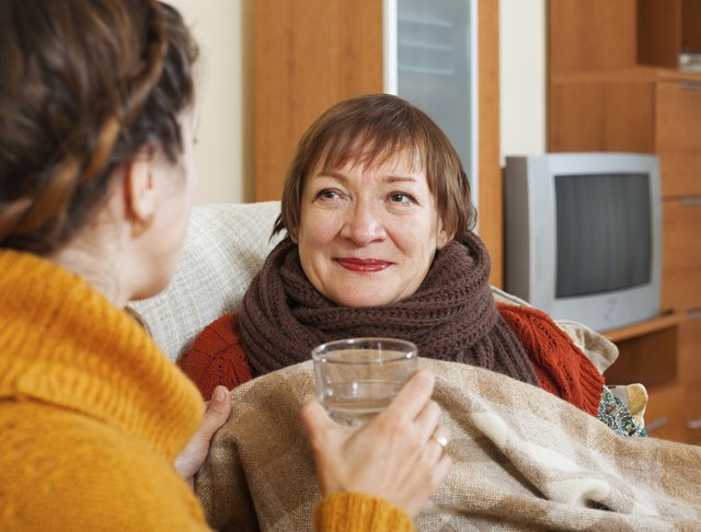 Adult woman caring for unwell senior mother