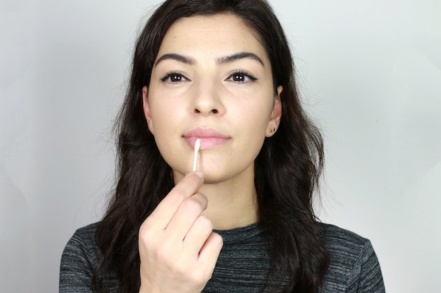woman exfoliating her lips
