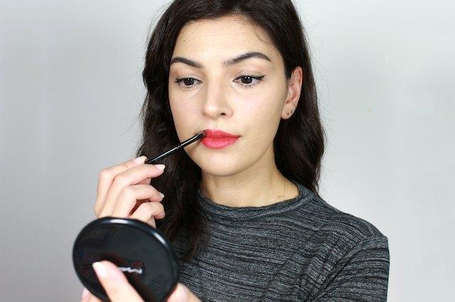 woman applying lipstick with a lip brush