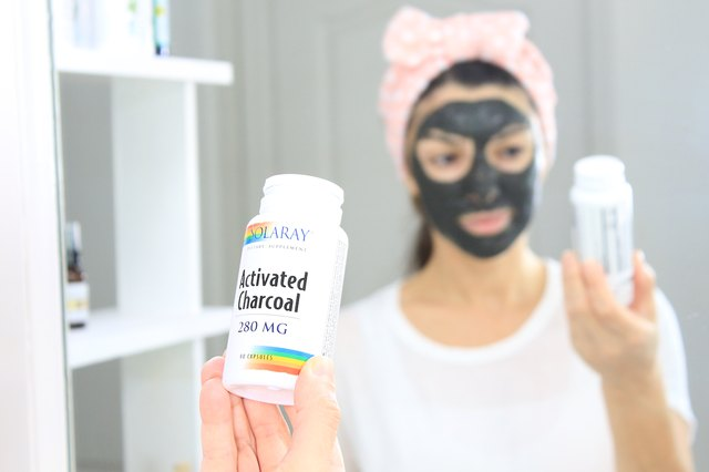 Woman wearing a face mask and holding an activated charcoal bottle