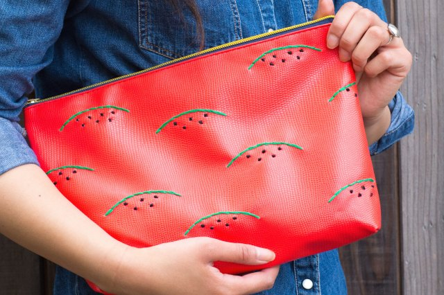 Woman holding embroidered watermelon clutch
