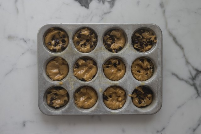 Divide the cookie dough between the cupcake pans.
