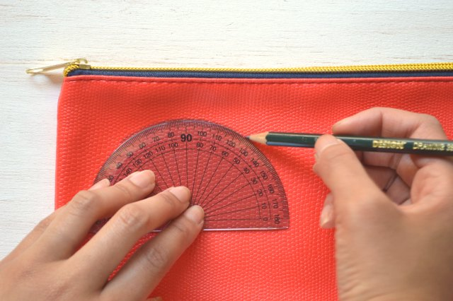 Holding the protractor in place while tracing the protractor