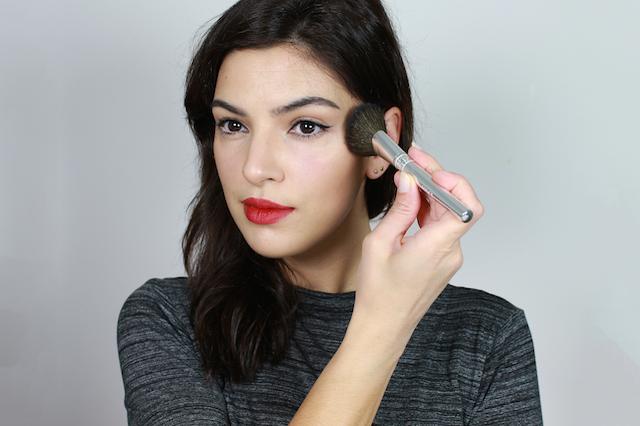 woman applying bronzer