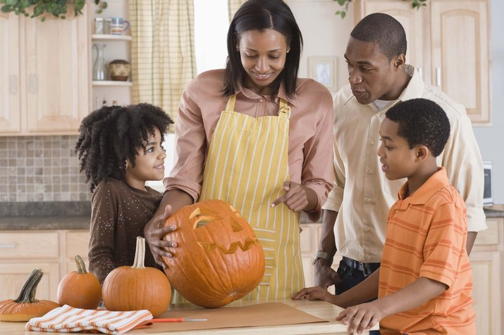 Family carving pumpkin in kitchen