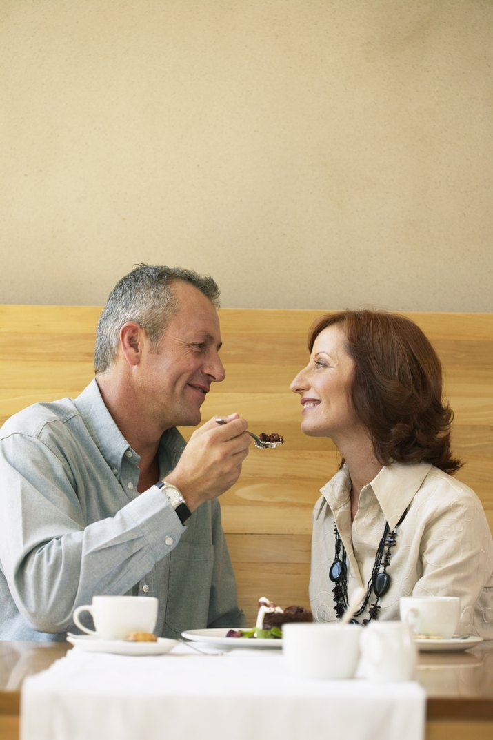 Couple sharing dessert, man spoon feeding woman, smiling at each other