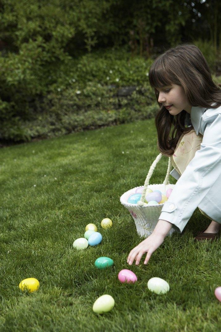 Girl (8-10) participating in Easter egg hunt, placing eggs in basket