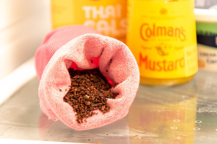 use a sock and coffee grounds to freshen the fridge
