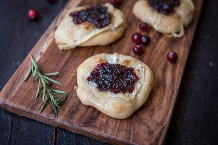 Cranberry brie flatbreads on a dark wood cutting board, with whole berries and a sprig of rosemary