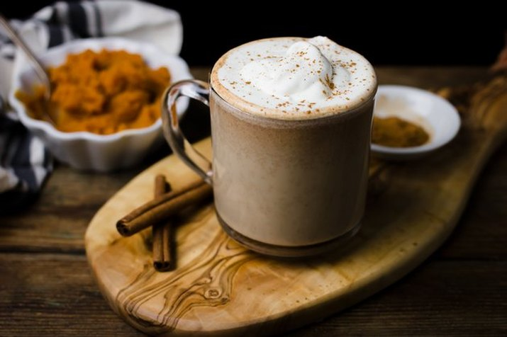 A pumpkin spice latte served in a glass mug on a cutting board, with spices and a dish of pumpkin puree visible in the background