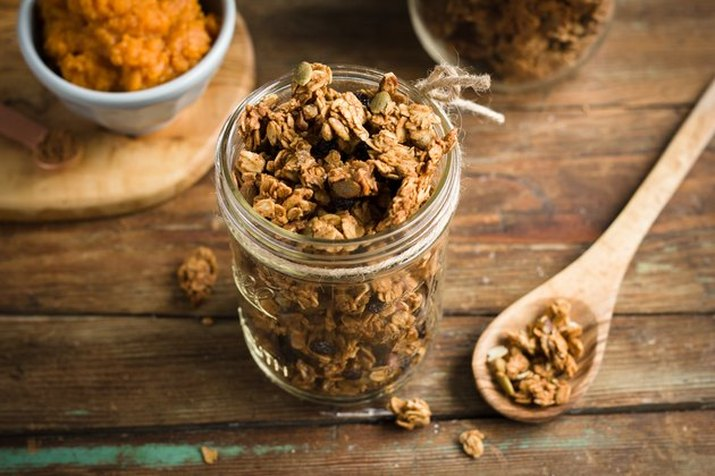 A mason jar full of pumpkin spice granola on a rustic table, with a wooden mixing spoon and a small bowl of pumpkin puree on either side