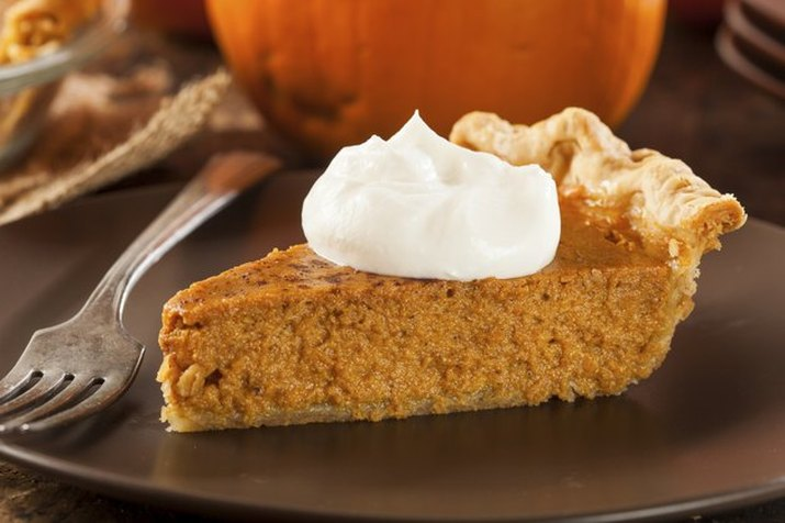 A slice of pumpkin pie, topped with whipped cream, on a dark plate with a whole pumpkin in the background